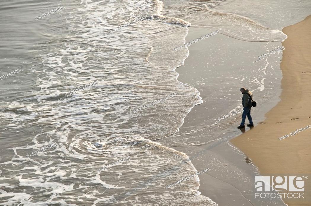Stock Photo: Man alone on south beach Tenby, Pembrokeshire, Wales, UK.