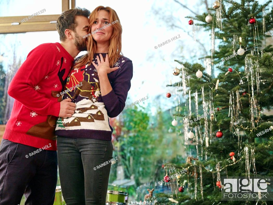 Stock Photo: Couple standing in front of Christmas tree, man kissing surprised woman.