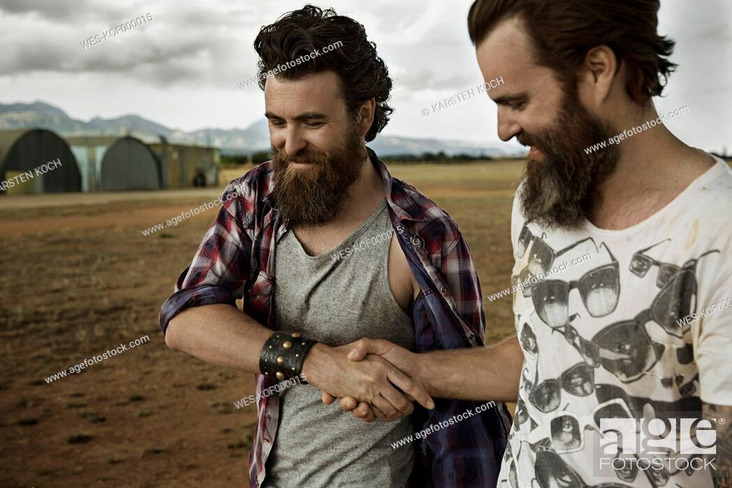 Stock Photo: Two men with full beards in abandoned landscape shaking hands.