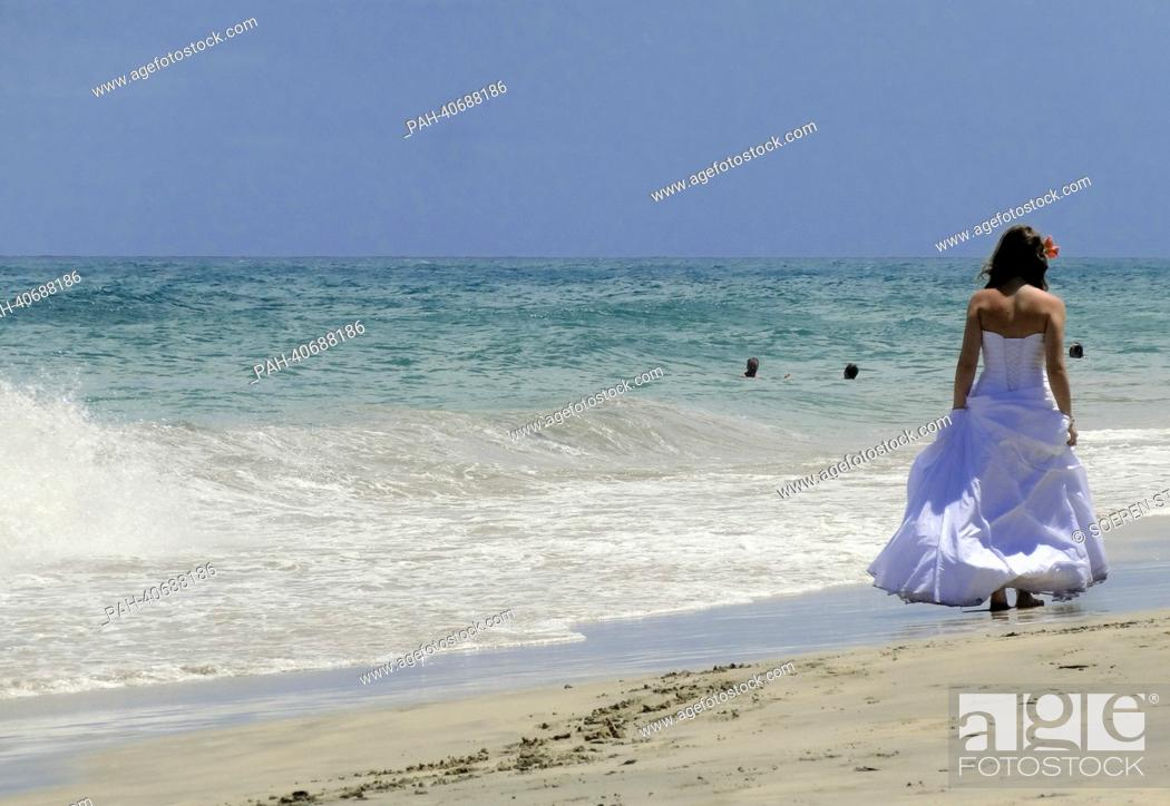 Stock Photo: A woman in a wedding dress walks along the sandy beach of Costa Calma on Fuerteventura, Spain, 05 June 2013. Photo:Soeren Stache | usage worldwide.