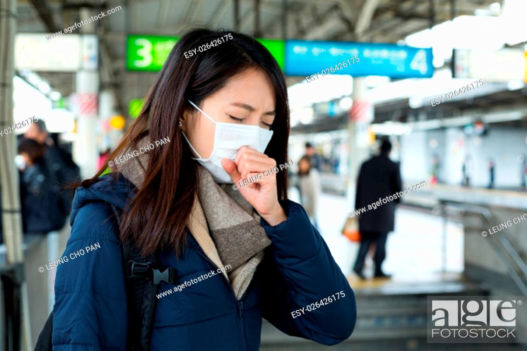 Stock Photo: Woman got sick and wearing face mask at train station.