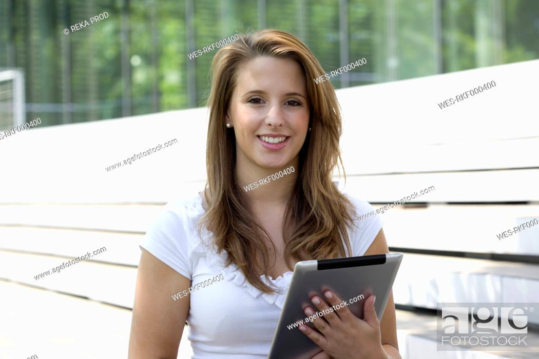 Stock Photo: Europe, Germany, North Rhine Westphalia, Duesseldorf, Young student with touchpad, smiling, portrait.
