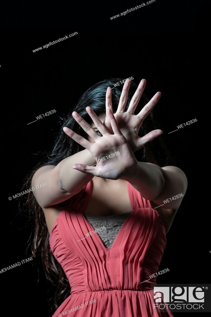 Stock Photo: Scared woman in danger hiding face with hands.