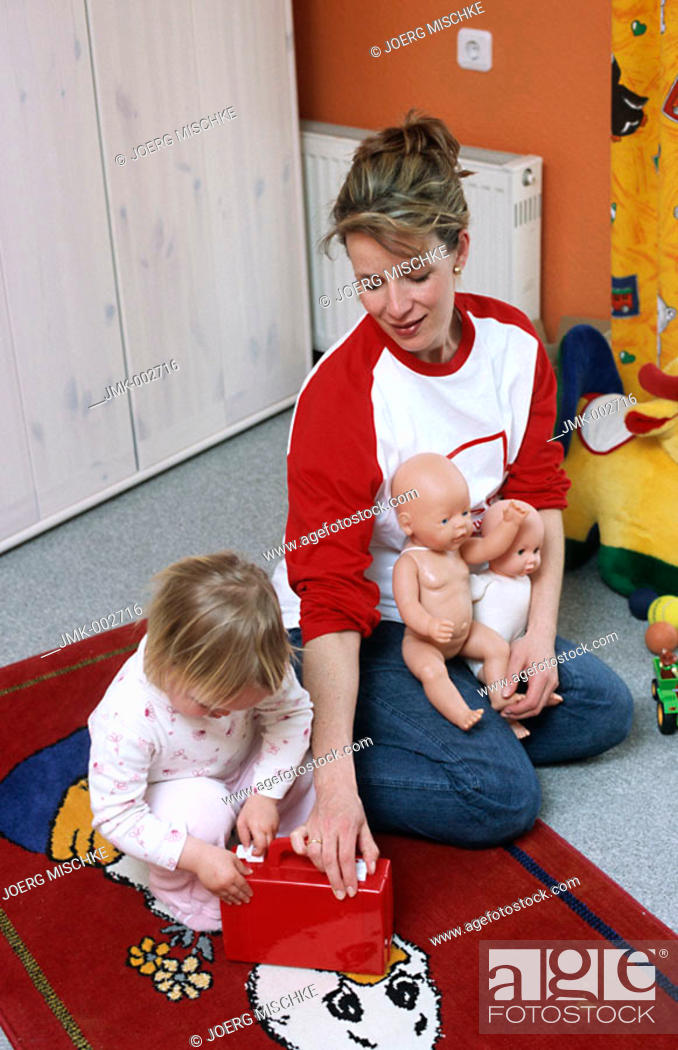 Stock Photo: A young pregnant mother, woman, 25-30 30-35 35-40 years old, playing with her little daughter, 1-5 years old, in the nursery.