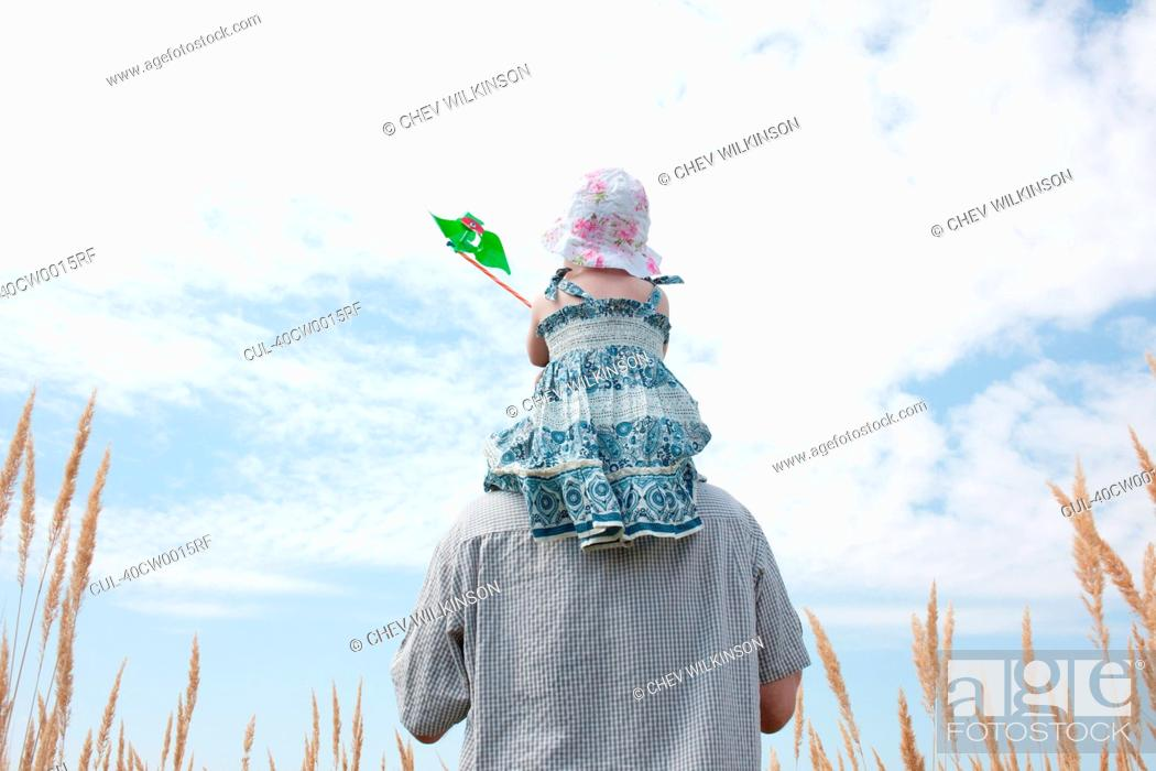 Stock Photo: Man carrying daughter on shoulders.