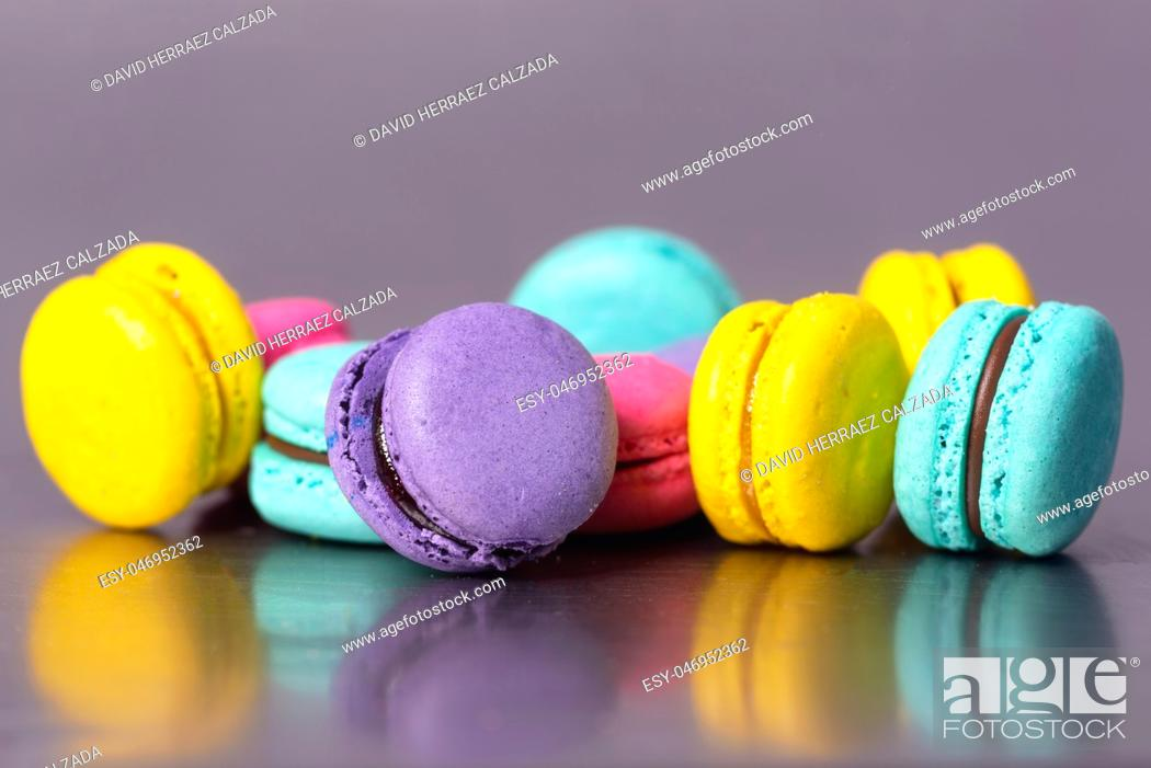 Stock Photo: Close up of colorful macarons dessert on purple background .
