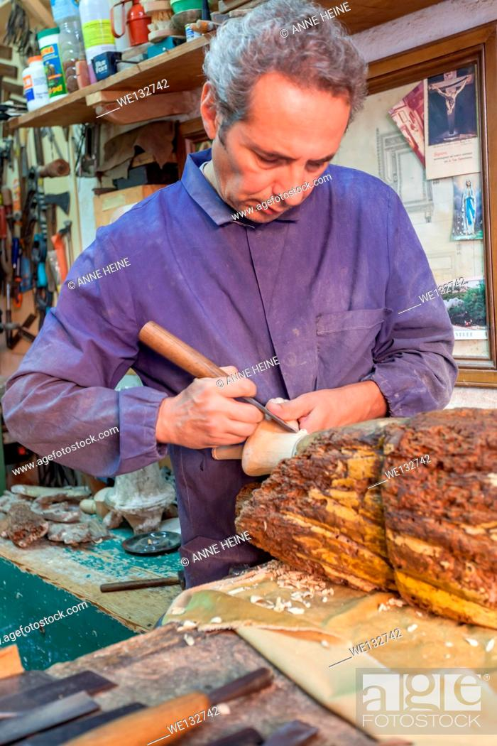 Stock Photo: A sardinian woodcarver in his traditional worshop carving a madonna (copy) from a chunk of wood, Cagliari, Italy.
