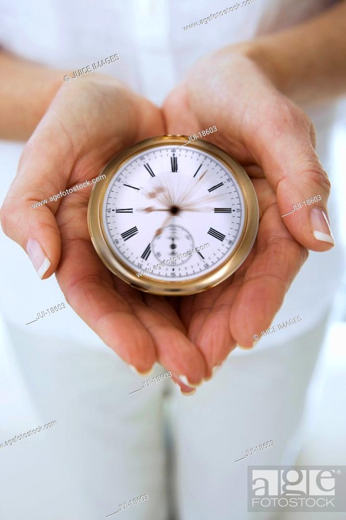 Stock Photo: Close up of womanÆs hands cupping stopwatch with moving hands.