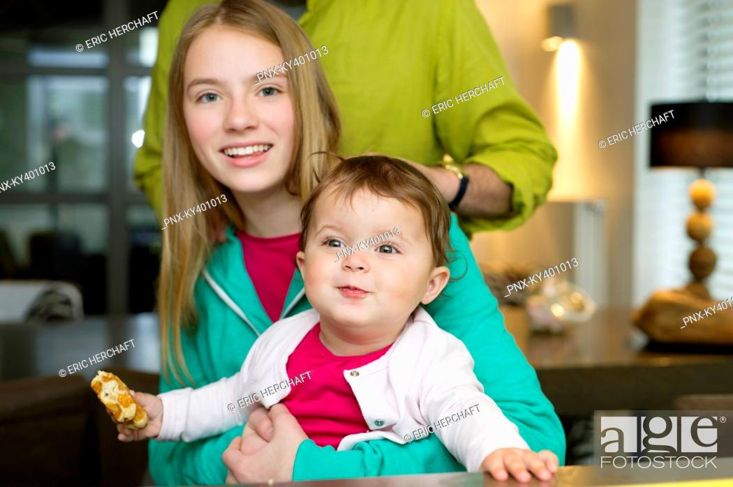 Stock Photo: Portrait of two girls with their father at home.