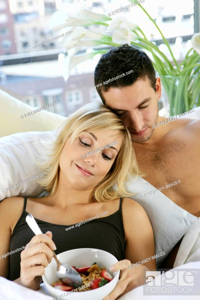 Stock Photo: Young couple eating breakfast in bed.