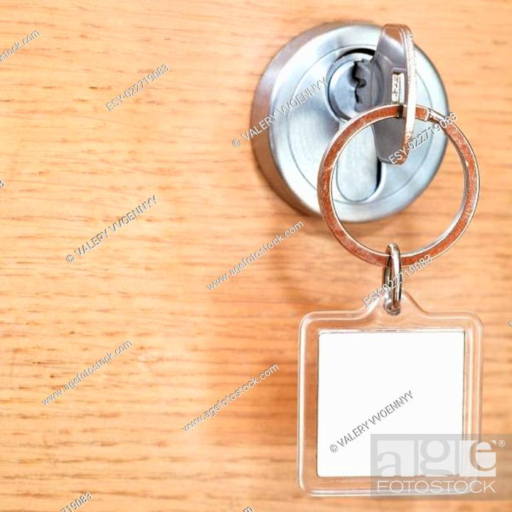 Photo de stock: key with blank square keychain in lock close up.