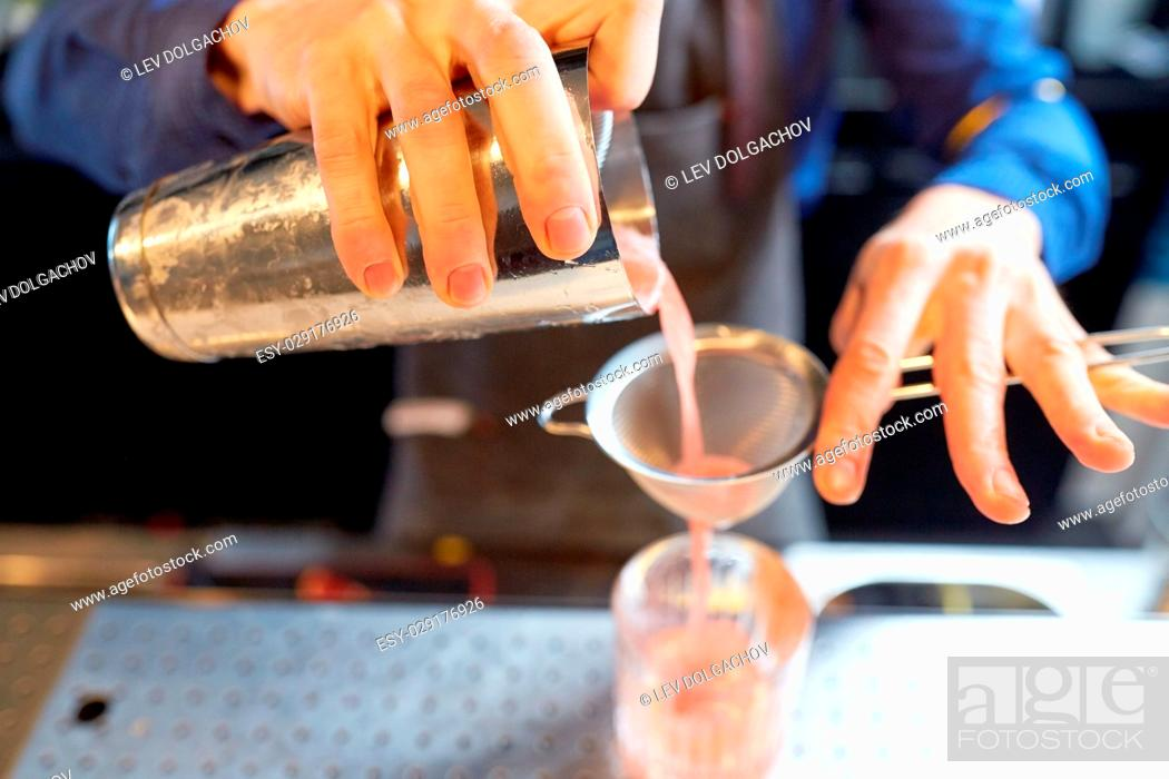 Stock Photo: alcohol drinks, people and luxury concept - barman pouring cocktail from shaker through strainer into glass at bar.