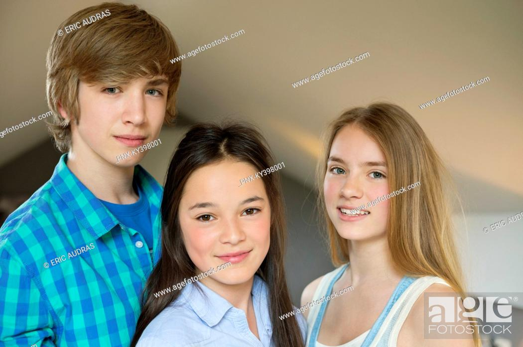 Stock Photo: Portrait of a teenage boy with his two sisters smiling.