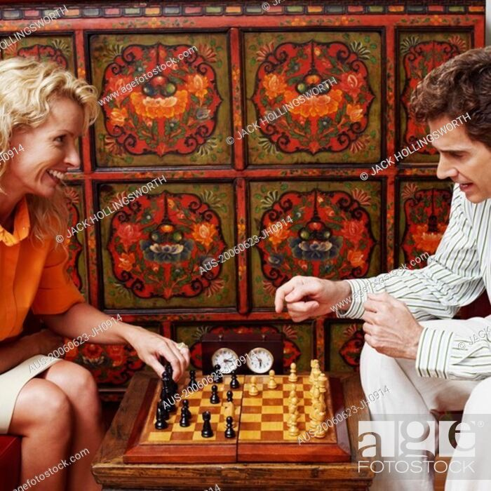 Imagen: Side profile of a businessman and a businesswoman playing chess.