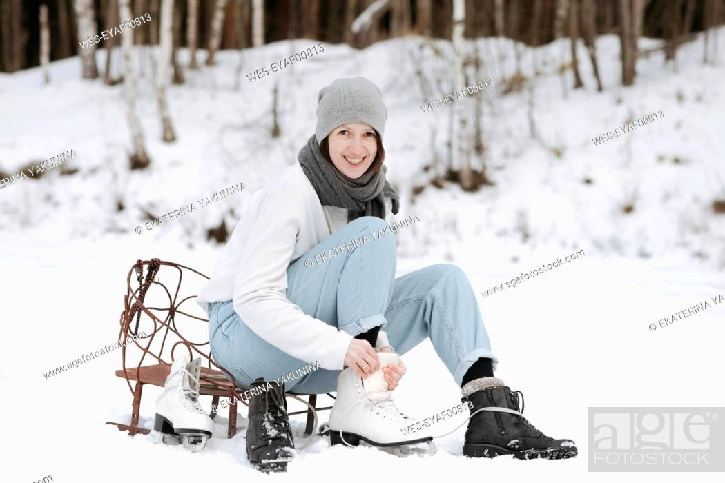 Photo de stock: Portrait of smiling woman putting on ice skates on snow field.