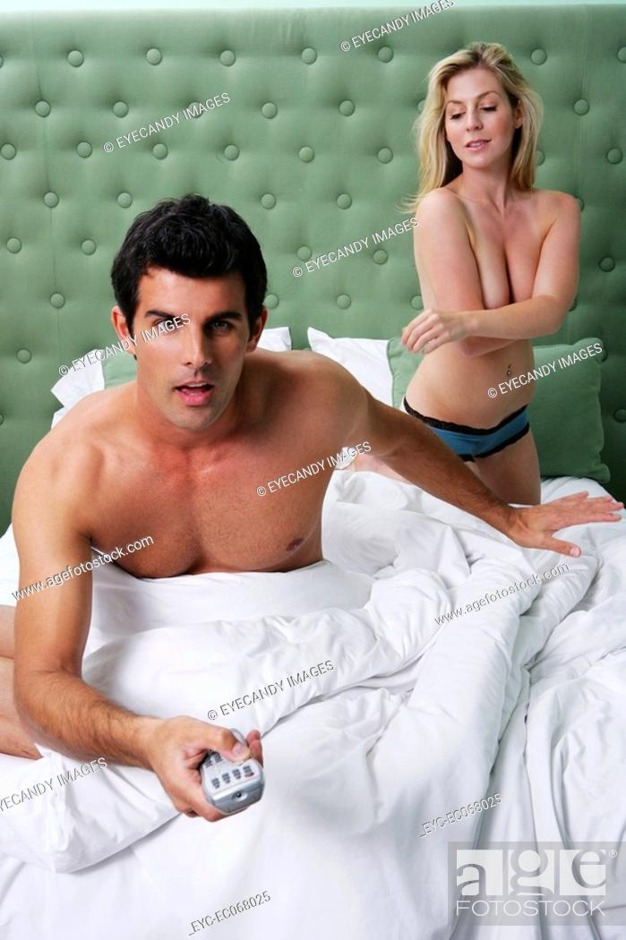 Stock Photo: Man watching TV in bed with topless woman in background.