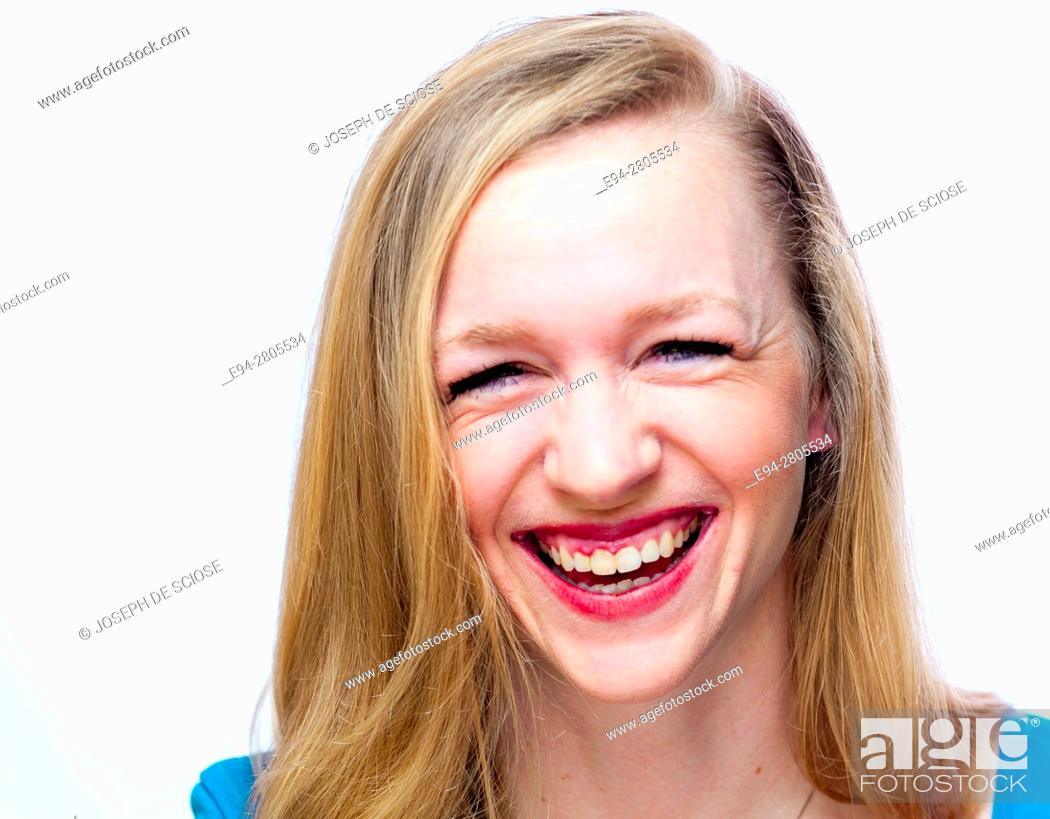 Stock Photo: A happy 25 year old blond woman smiling at the camera with squinting eyes.