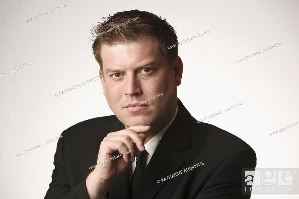 Stock Photo: Man with hand on chin thinking, wearing black suit and tie.