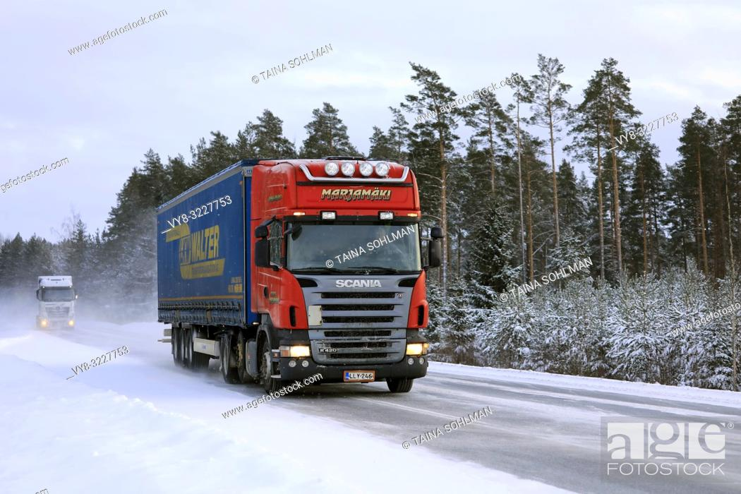 Stock Photo: Salo, Finland - January 18, 2019: Red Scania R420 semi trailer Marjamaki and another truck drive on snowy winter highway in South of Finland.
