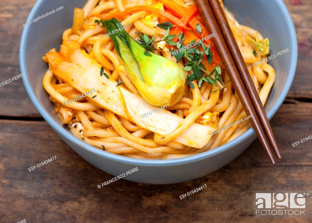 Stock Photo: hand pulled stretched Chinese ramen noodles on a bowl with chopstick.