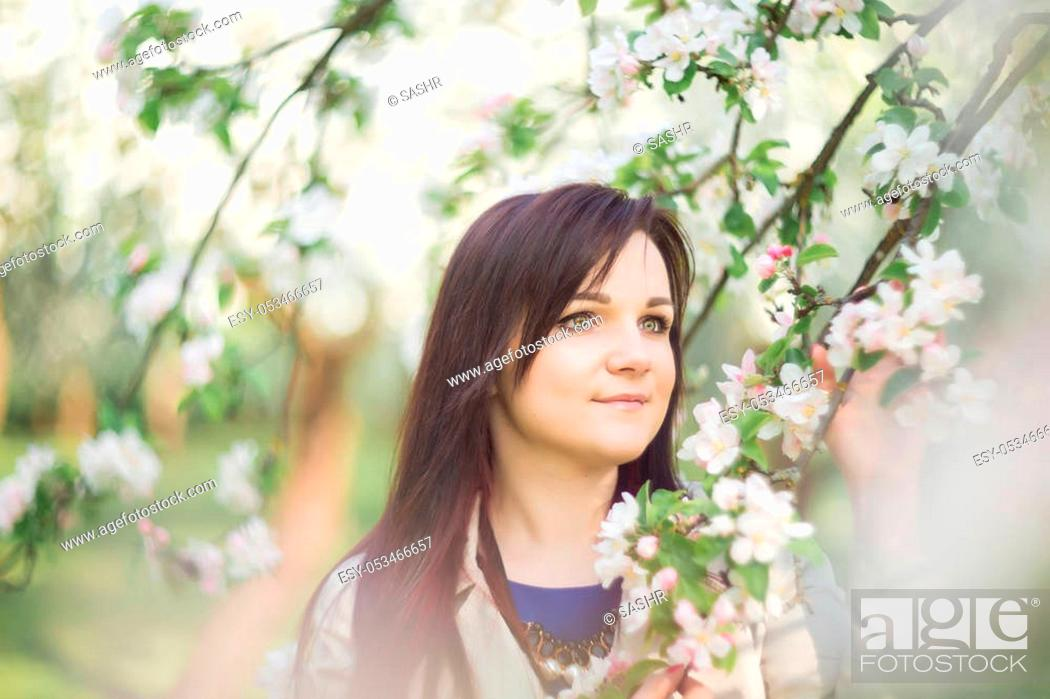 Stock Photo: beautiful young brunette woman standing near the blossoming apple tree on a warm spring day.