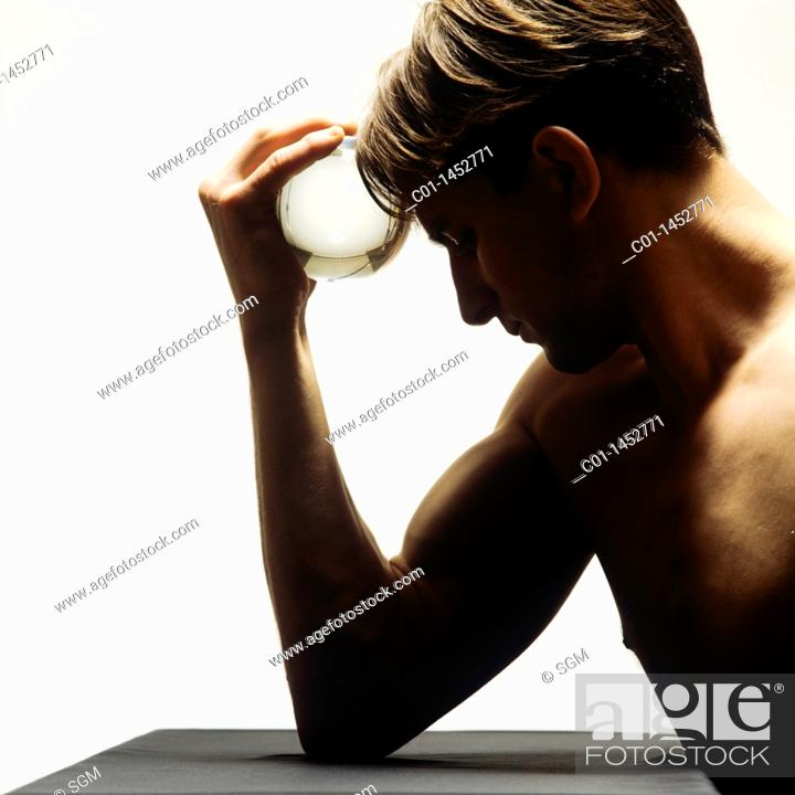 Stock Photo: Man holding a ball of glass against his forehead.