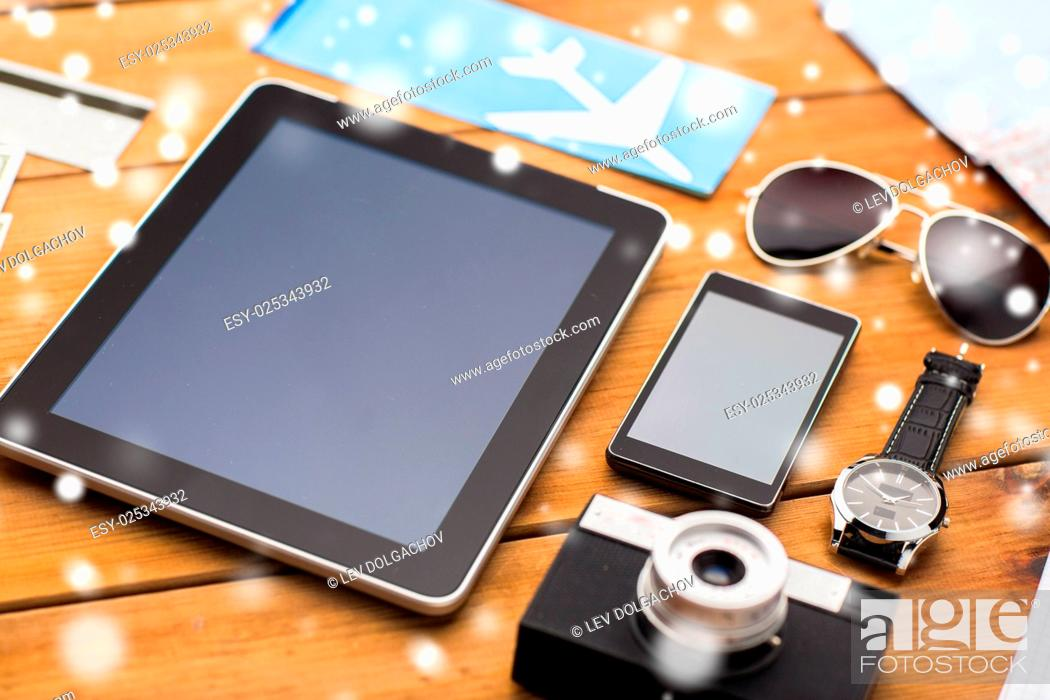 Stock Photo: travel, tourism, technology and winter holidays concept - smartphone with tablet pc computer, airplane ticket and personal stuff over snow.