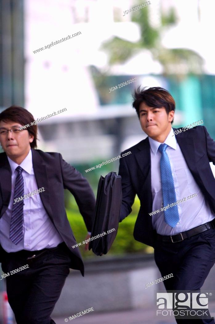 Stock Photo: Two businessmen holding briefcase and running together.