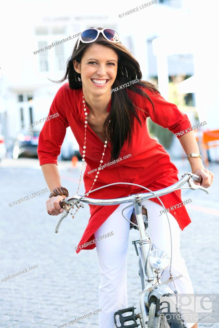 Stock Photo: Portrait of a beautiful young woman cycling.