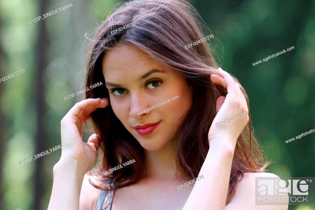 Stock Photo: Close-up face of beautiful girl straightens her hair.
