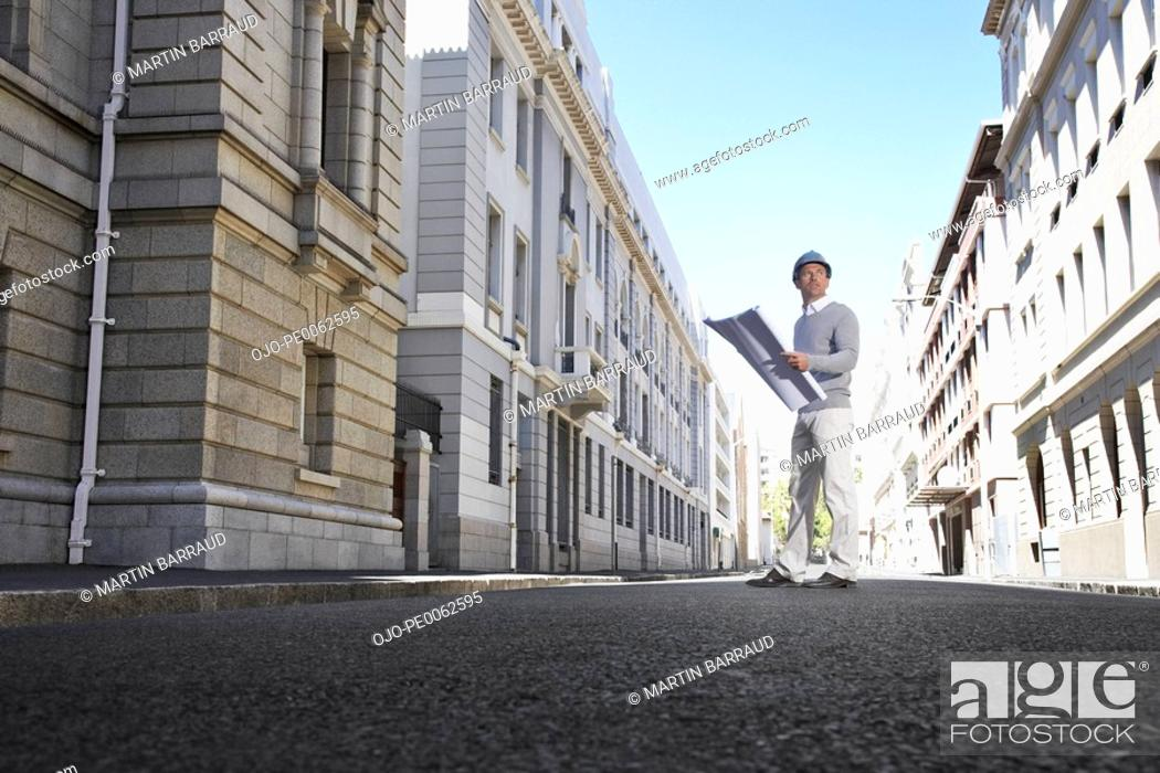 Stock Photo: Architect with blueprints on urban street.