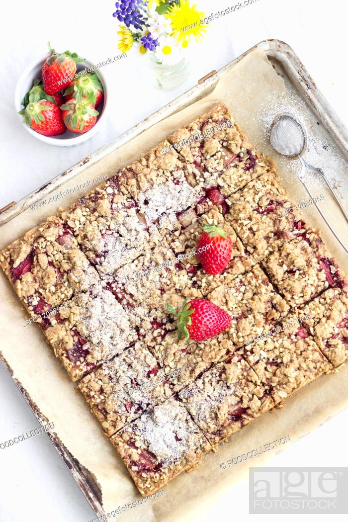Photo de stock: Strawberry crumble slices on a baking tray.