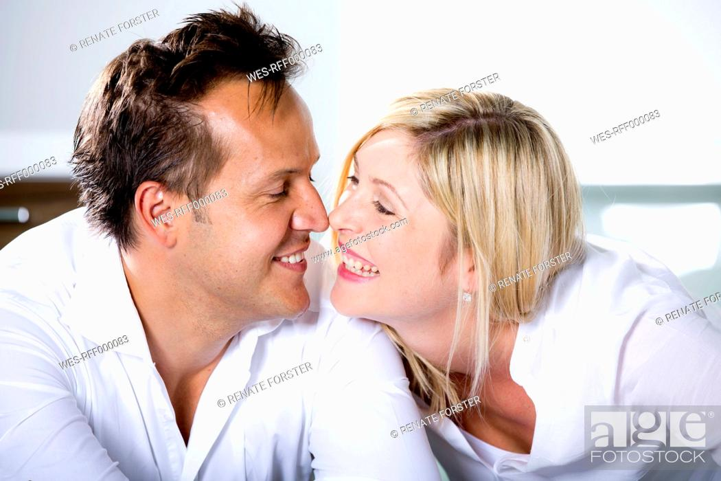 Stock Photo: Germany, Mid adult couple touching nose, smiling.