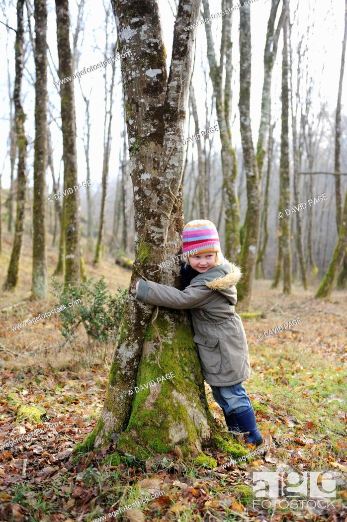 Stock Photo: Five year old girl hugging a tree.