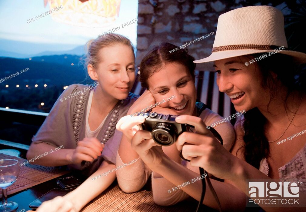 Stock Photo: Three women looking at digital pictures.