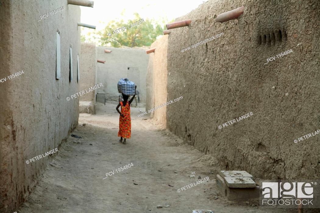 Stock Photo: Rear view of a woman walking on street in Djenne, Mali.