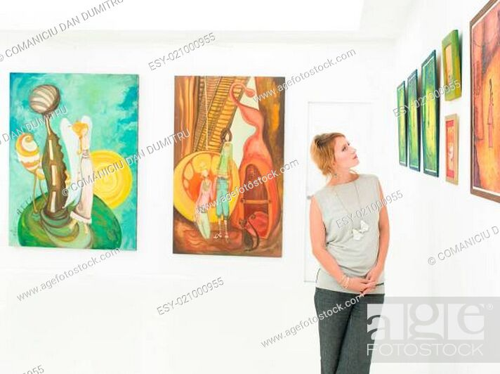 Imagen: side view of young beautiful woman standing in an art gallery contemplating paintings displayed in front of her.