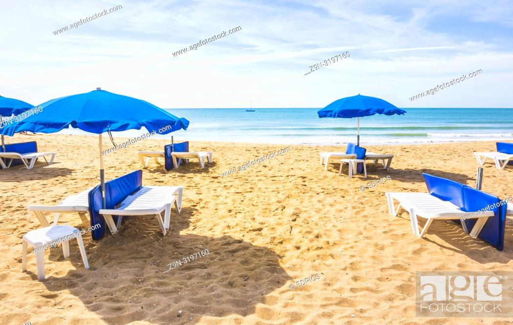 Stock Photo: blue umbrellas and sun chairs at deserted beach, albufeira, algarve, portugal.