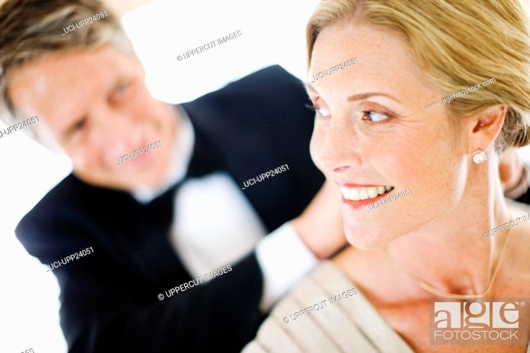 Stock Photo: Man in tuxedo fastening necklace on woman.