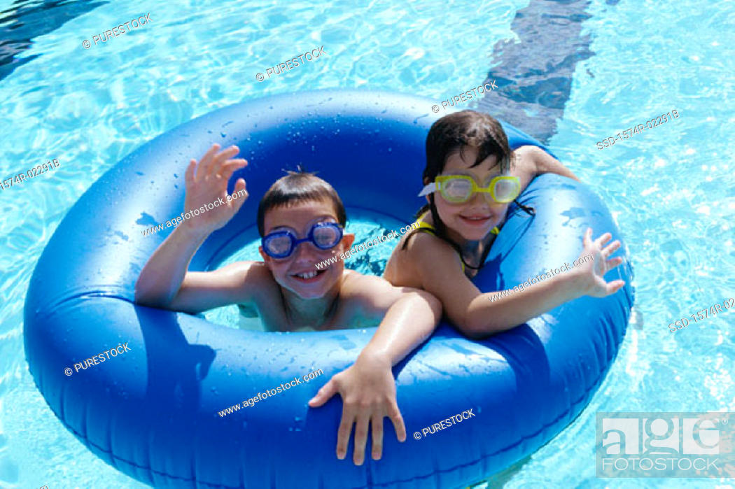 Stock Photo: High angle view of a boy and a girl in an inflatable ring in a swimming pool.