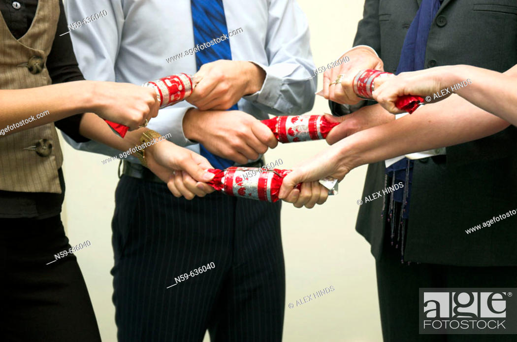 Stock Photo: Diverse business team having fun pulling crackers at their office Christmas party.