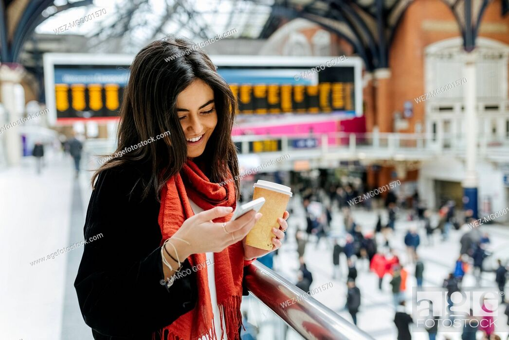 Imagen: UK, London, Young woman using mobile phone at train station.