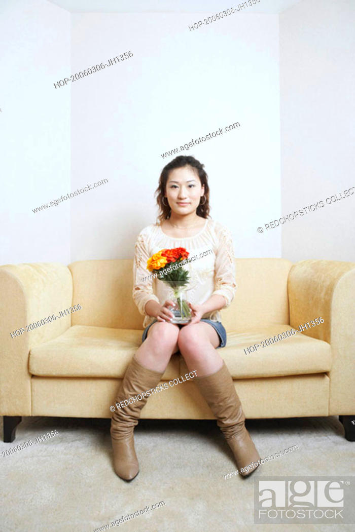 Stock Photo: Portrait of a young woman sitting on a couch holding a flower pot.