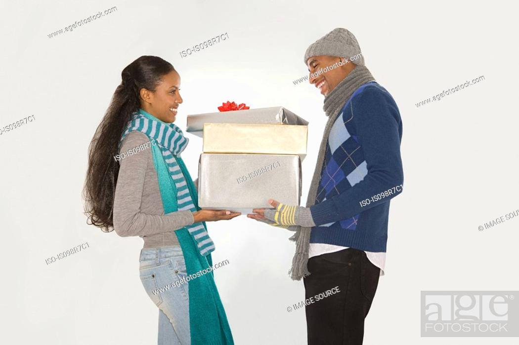 Stock Photo: Couple holding christmas gifts.