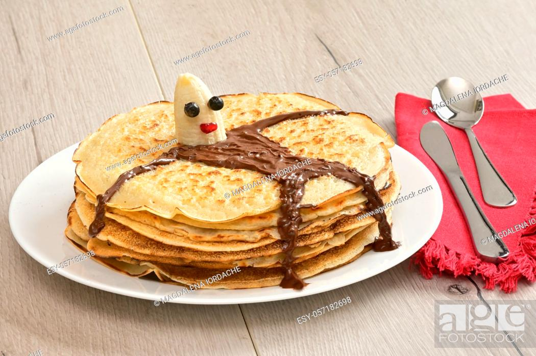 Stock Photo: Pile Of Baked Pancakes and Banana Character Lying on Pancakes.