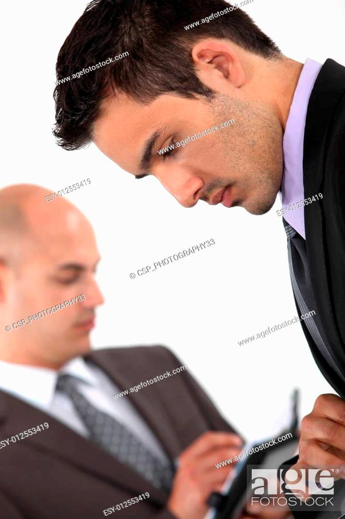 Stock Photo: Two businessmen checking their schedules.