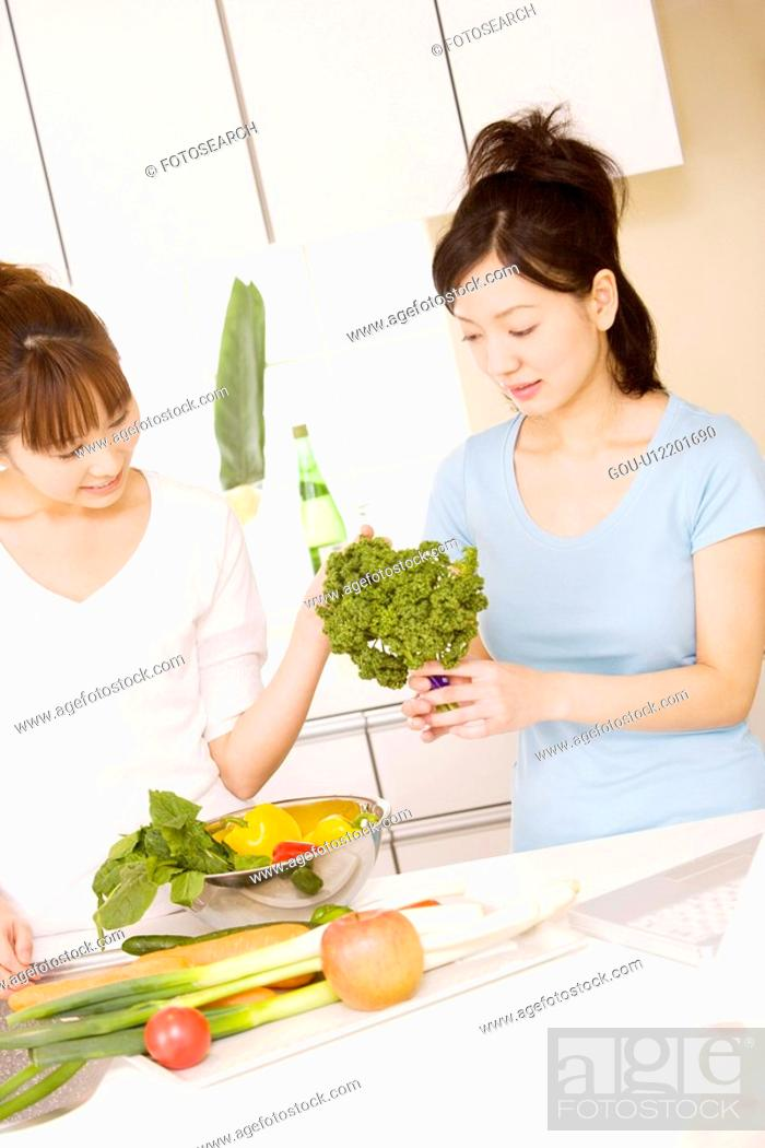 Stock Photo: Two women cooking vegetables.