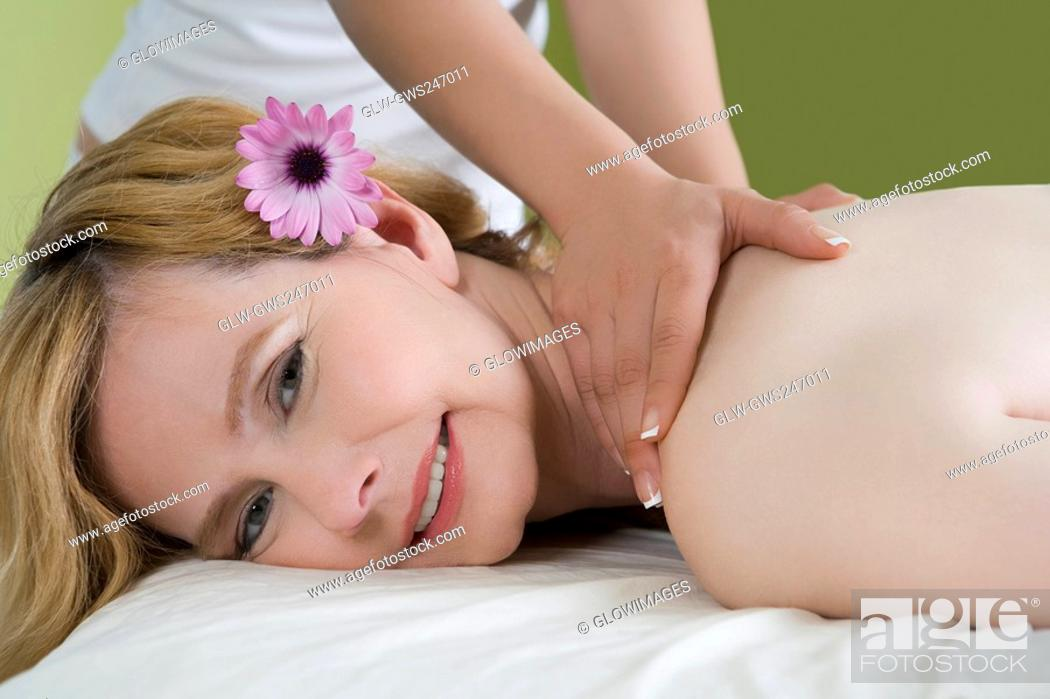 Stock Photo: Portrait of a mature woman getting a shoulder massage from a massage therapist.