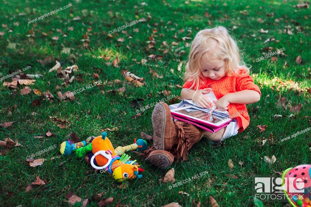 Imagen: Girl sitting on grass with toys looking down using digital tablet.