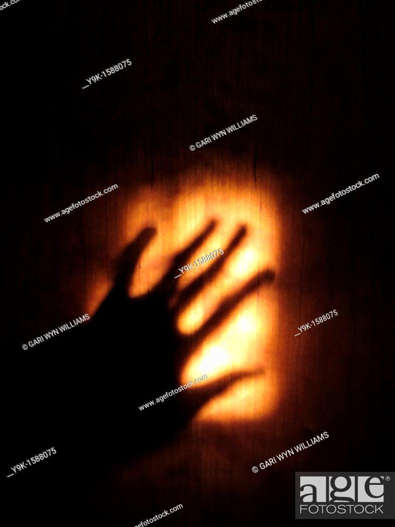 Stock Photo: Shadow of hand on wooden door.